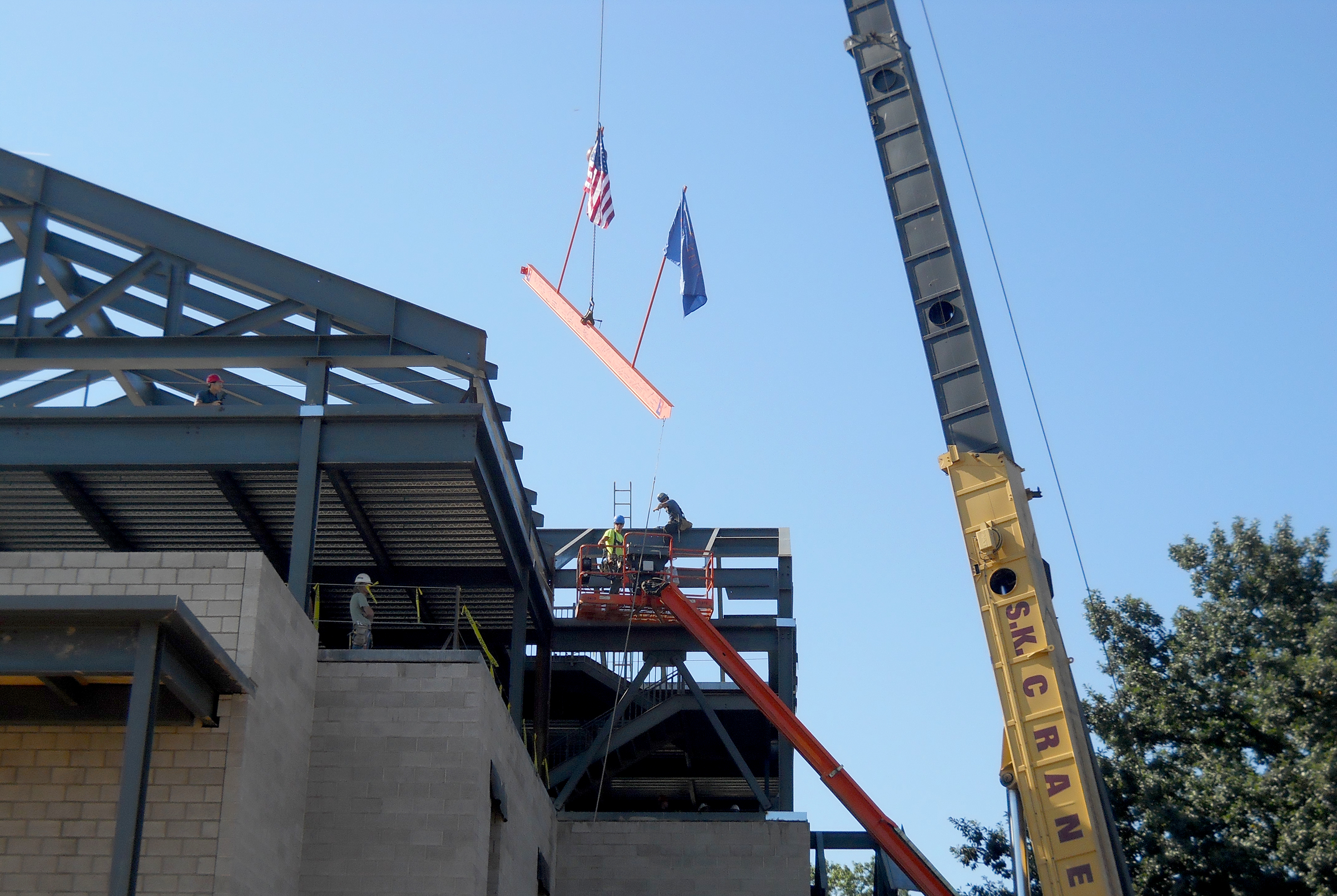 The final piece of steel is flown into place at the Academic West building of Bucknell University.