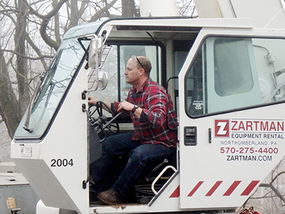 A Zartman Construction crane operator works one of the team