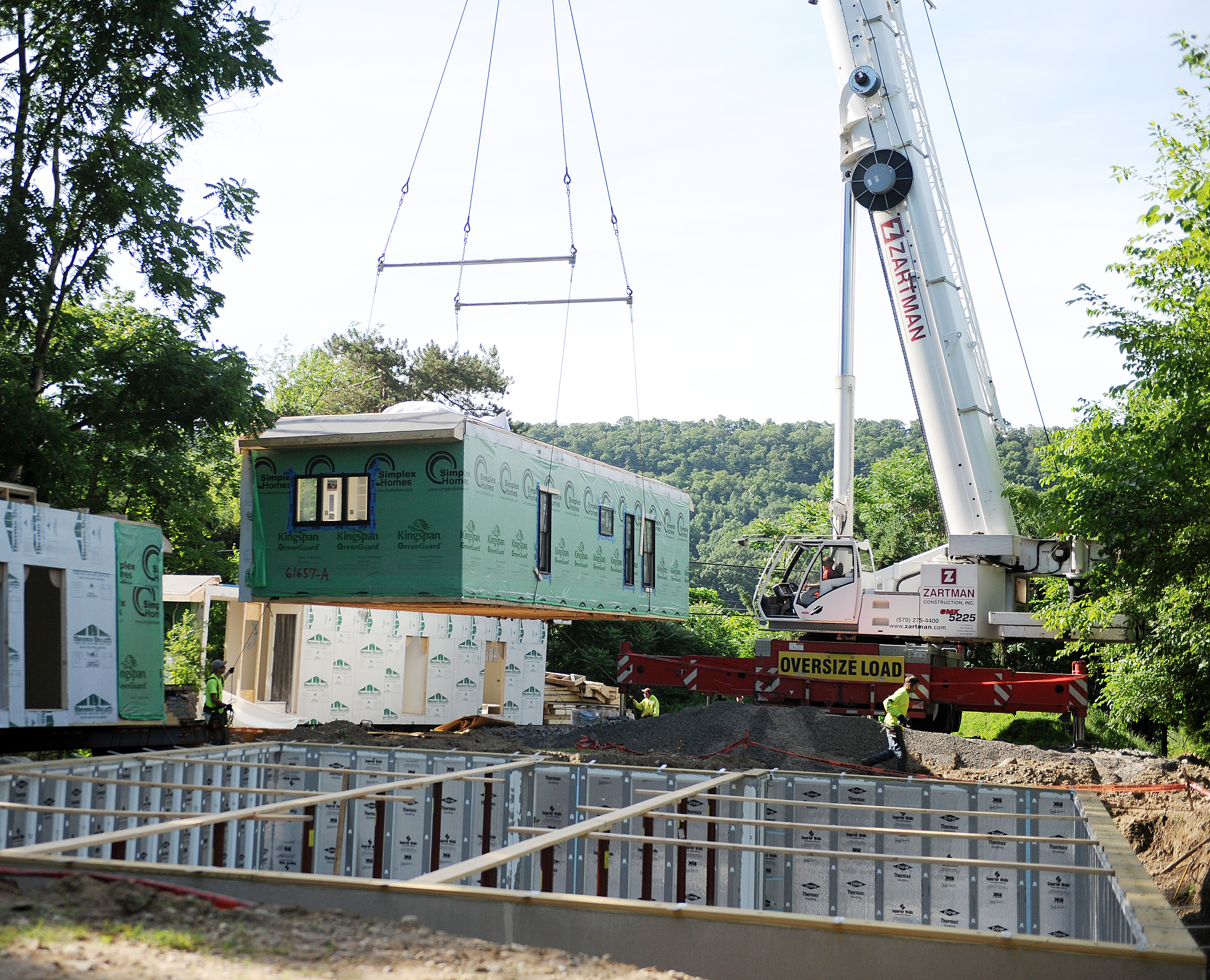 A section of modular home is set with a 140 ton crane.