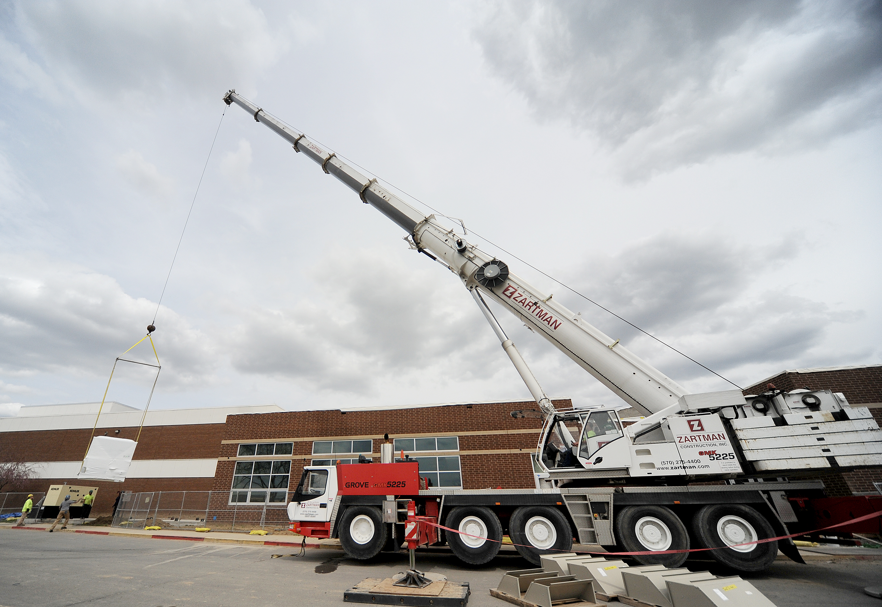A piece of HVAC equipment is set into place with a 225 ton crane.