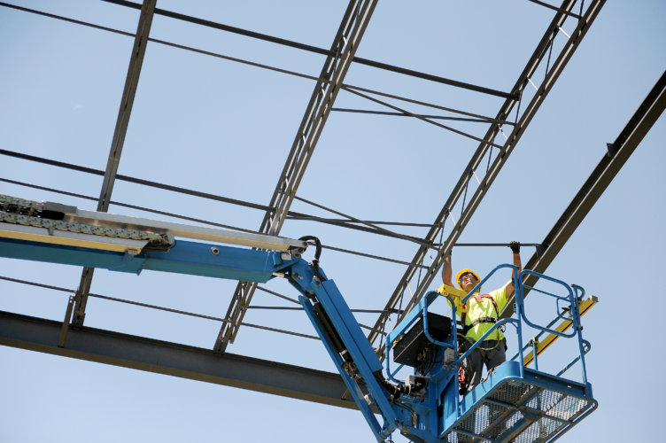 A Zartman Construction worker puts together part of the roof of a new distribution facility.
